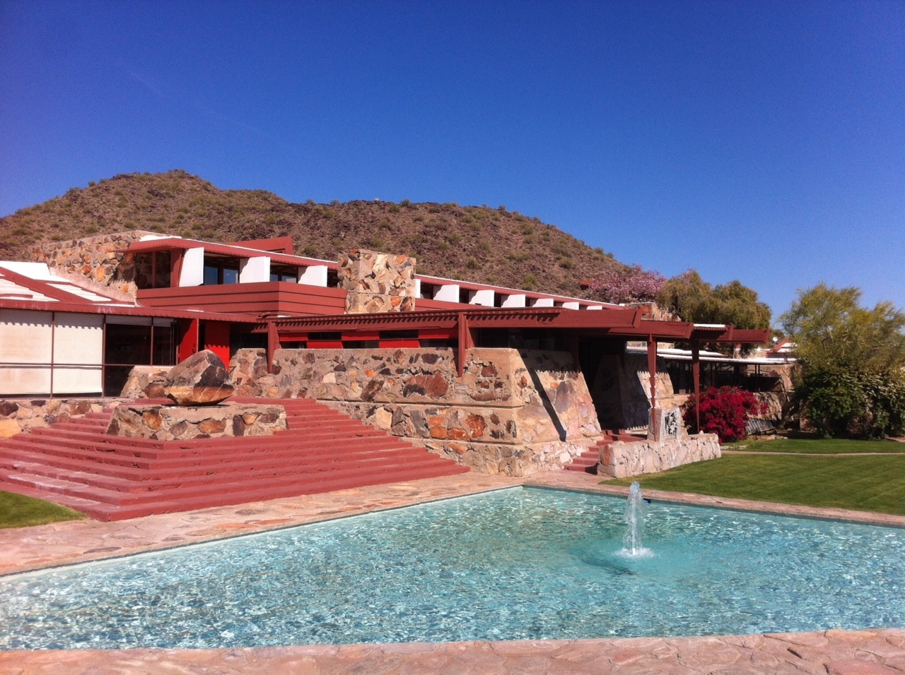 The Frank Lloyd Wright house with pool and front lawn looks more like a resort than a home. It is a good example of Prairie Modernism design with its flat roof, strong horizontal lines and broad overhanging eaves. This school of architecture was inspired by the strong horizontal horizon line and the flatness of the prairie landscape.
