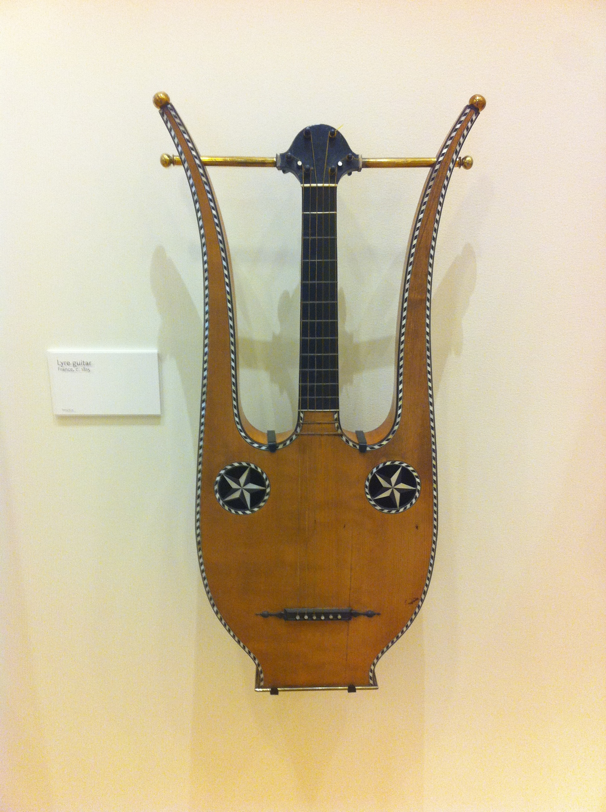 Lyre guitar, France, c. 1815. I loved the mask, folk-art quality of this guitar