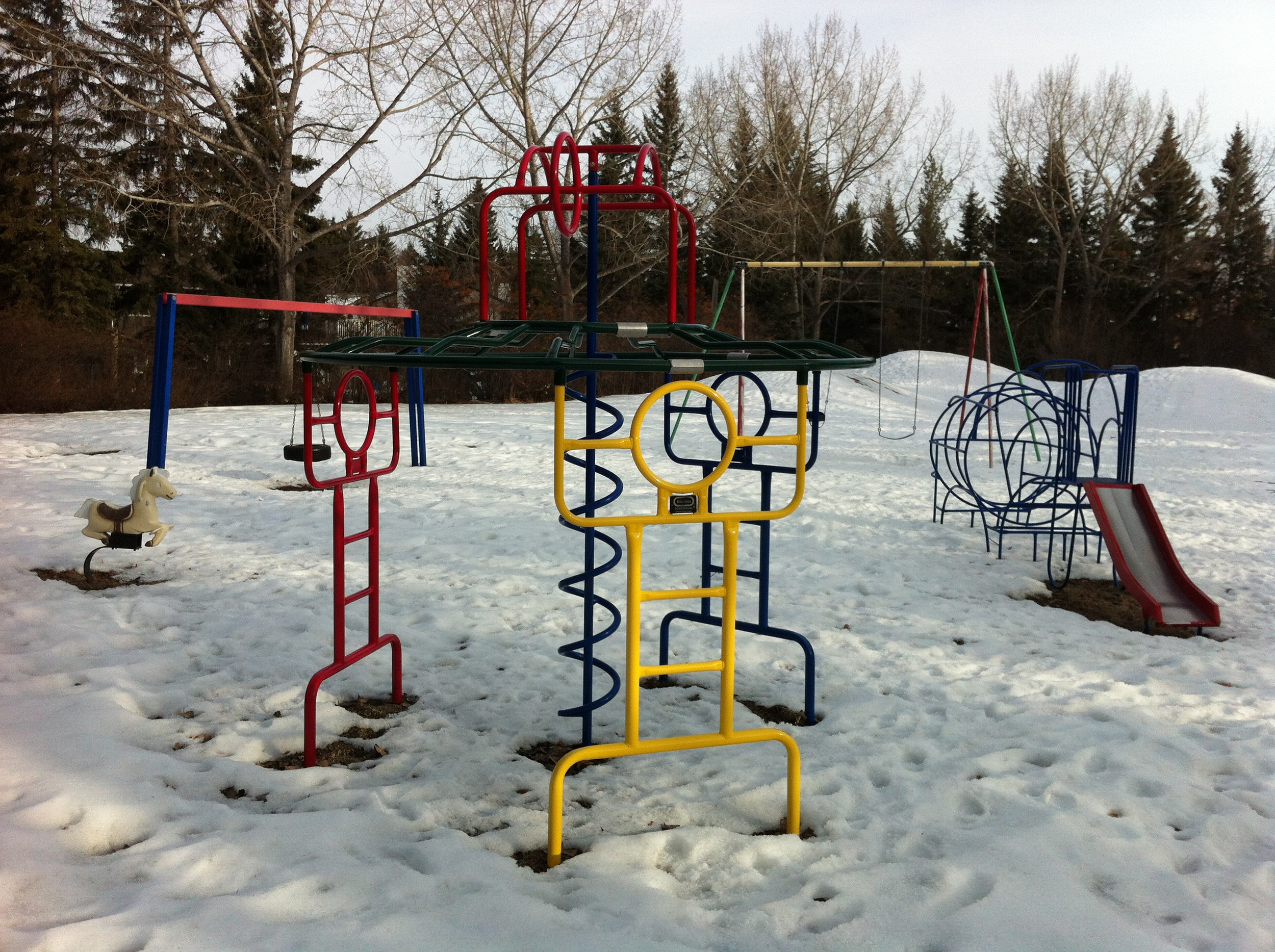 Lakeview's hidden playground with simple retro playground equipment - rocking horse and small metal slide.