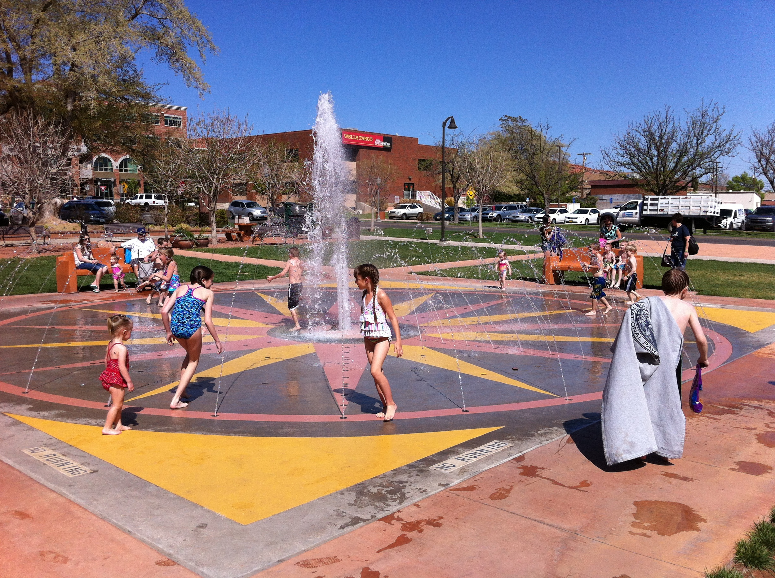 The water fountain is right next to the sidewalk and open to the street so pedestrian and drives can see all the fun being had by the families.