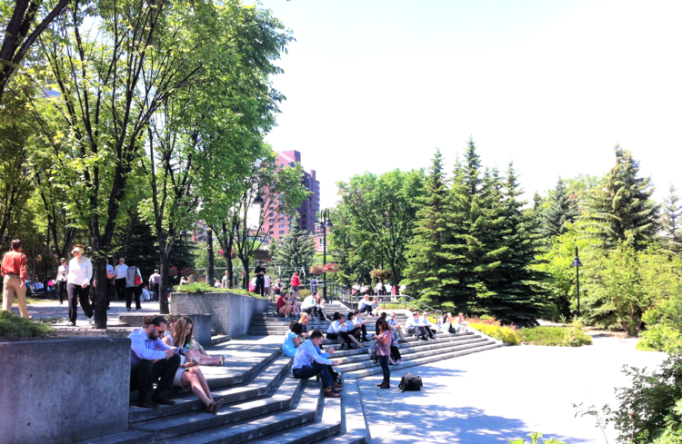 Downtown employees enjoy some sun and people watching along the Bow River Promenade and Prince's Island park.