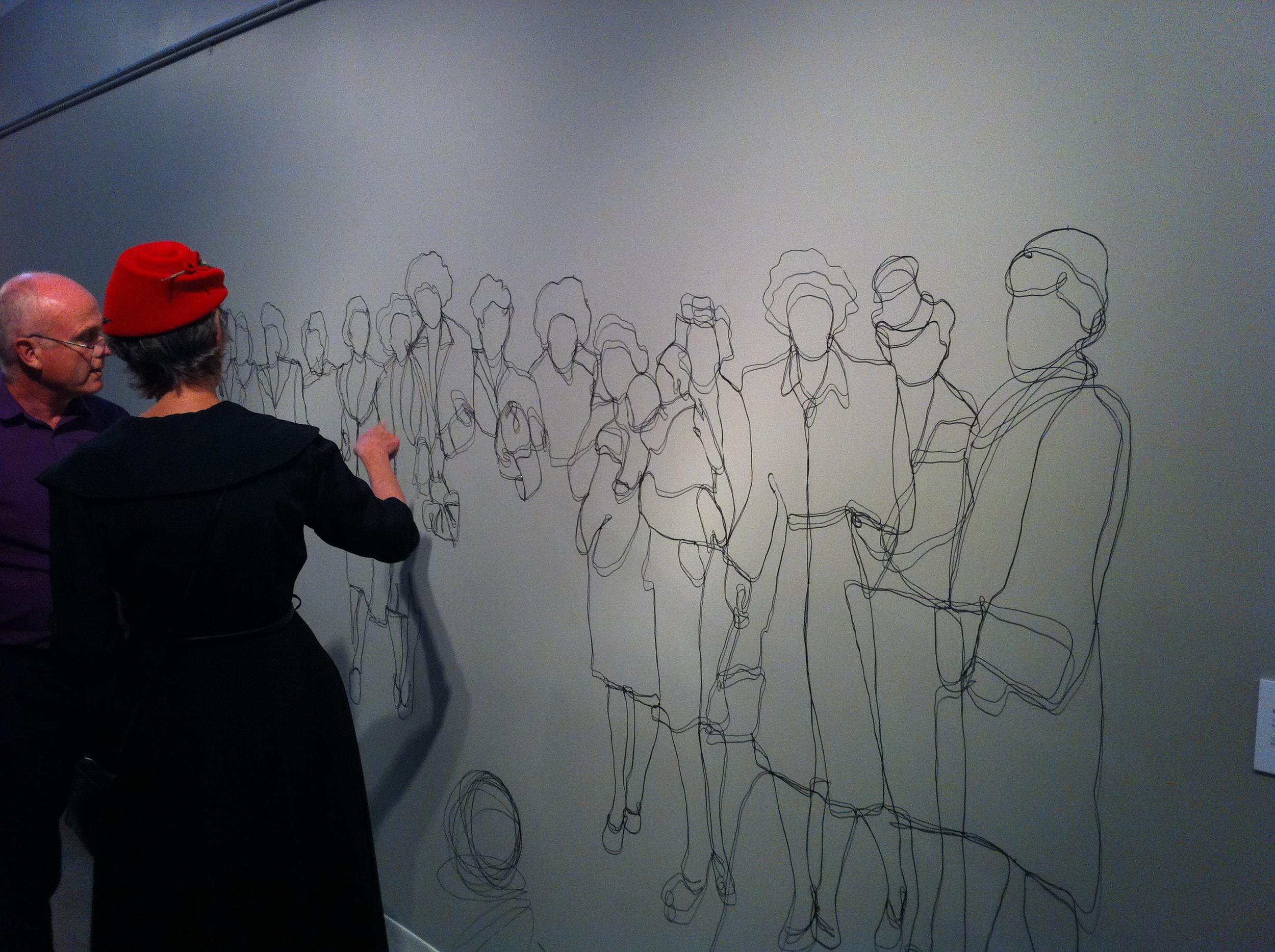 "Bev Tosh discussing her steel wire drawing ""Tug of War."""