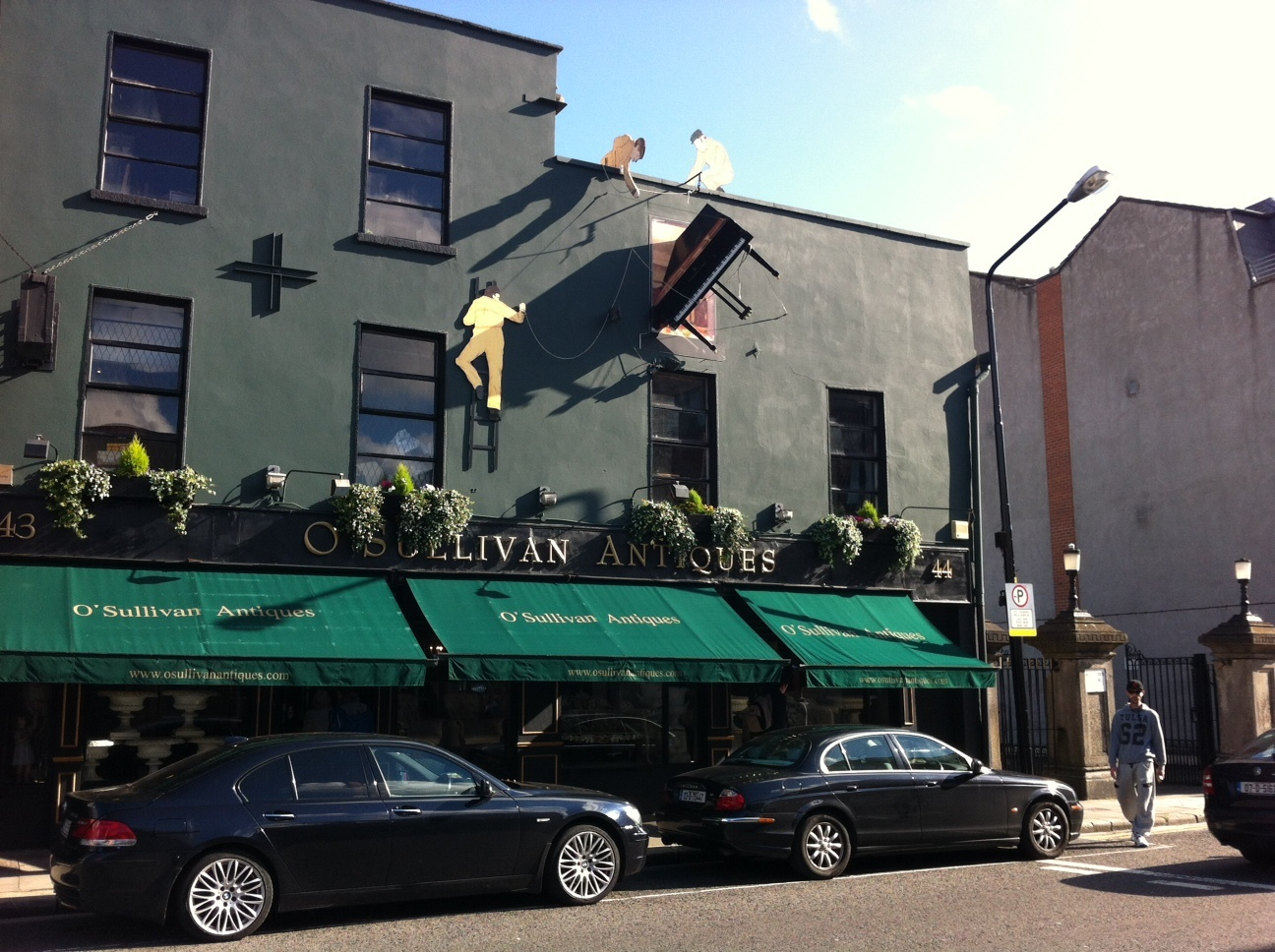 O'Sullivan's Antiques with funky delivery men climbing the wall with the dangling piano.