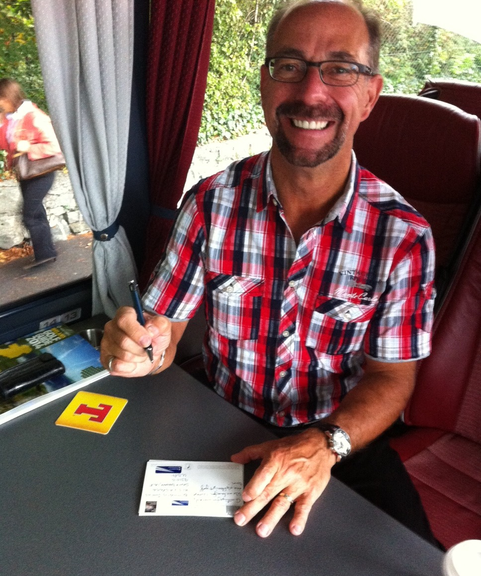 Postcard Willie writing postcards on the Dunbar Golf Tour bus between rounds.