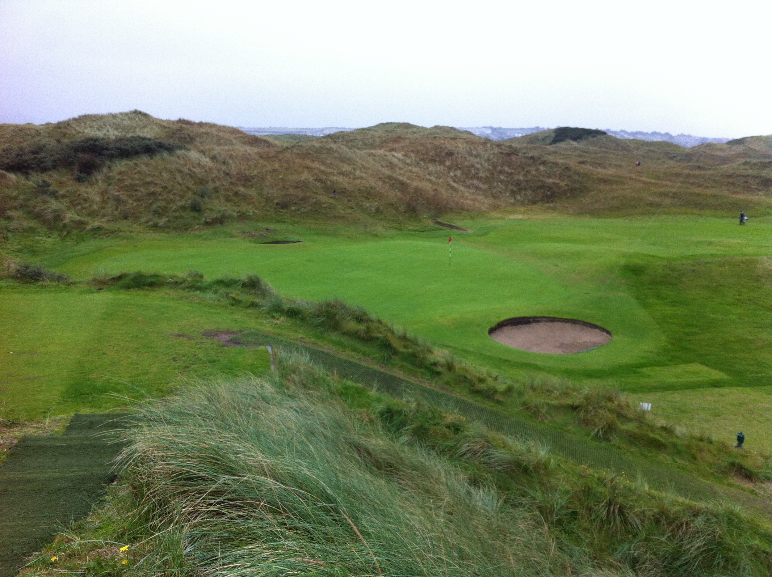 A typical hole with elevated tee boxes, fairways guarded by sand dunes and larger undulating crowned greens where the ball rolls off the green into a collection area also called a bunker.
