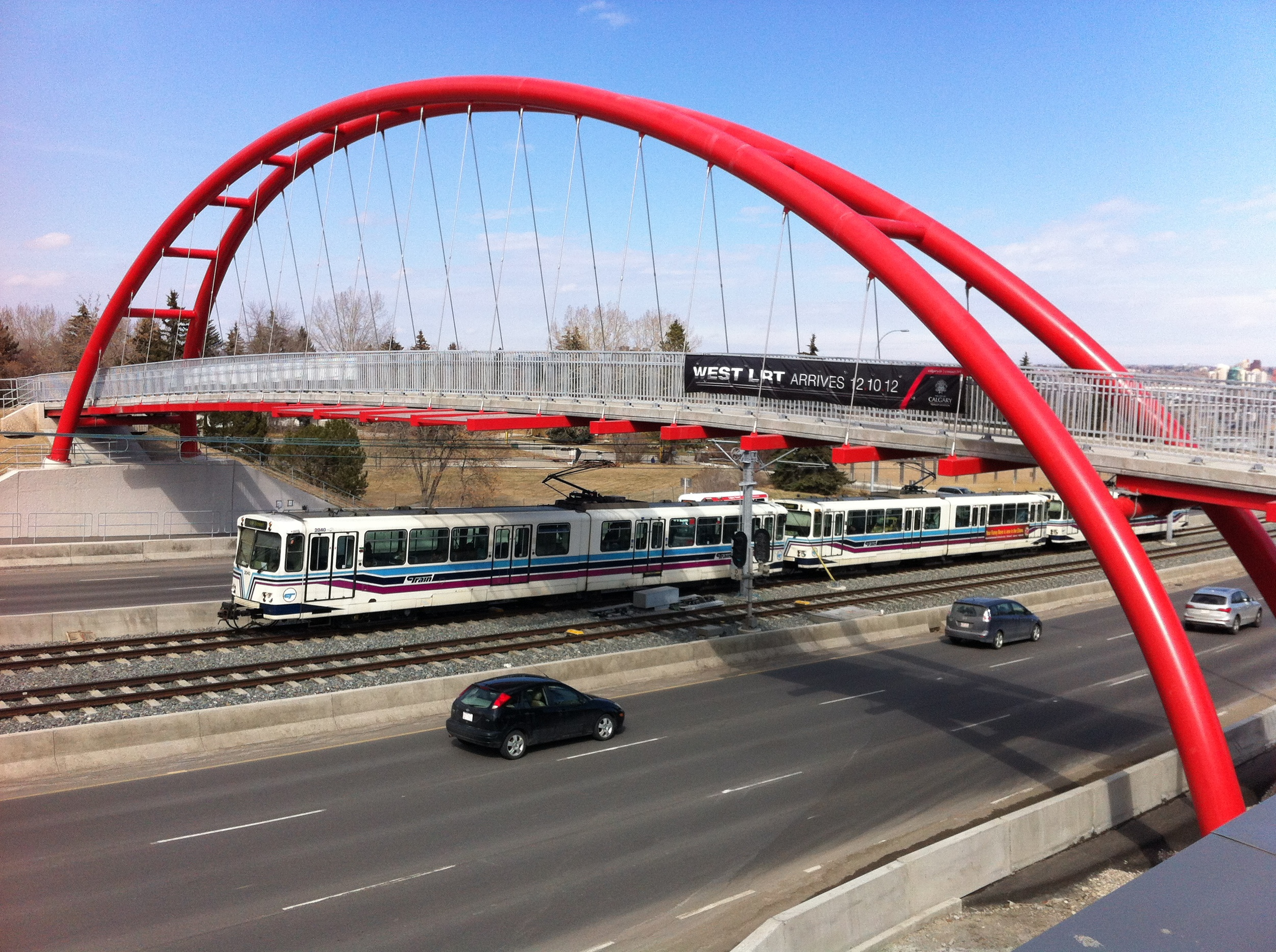 The bridge spans the river of buses, trains and automobiles entering and exiting the Downtown along Bow Trail.