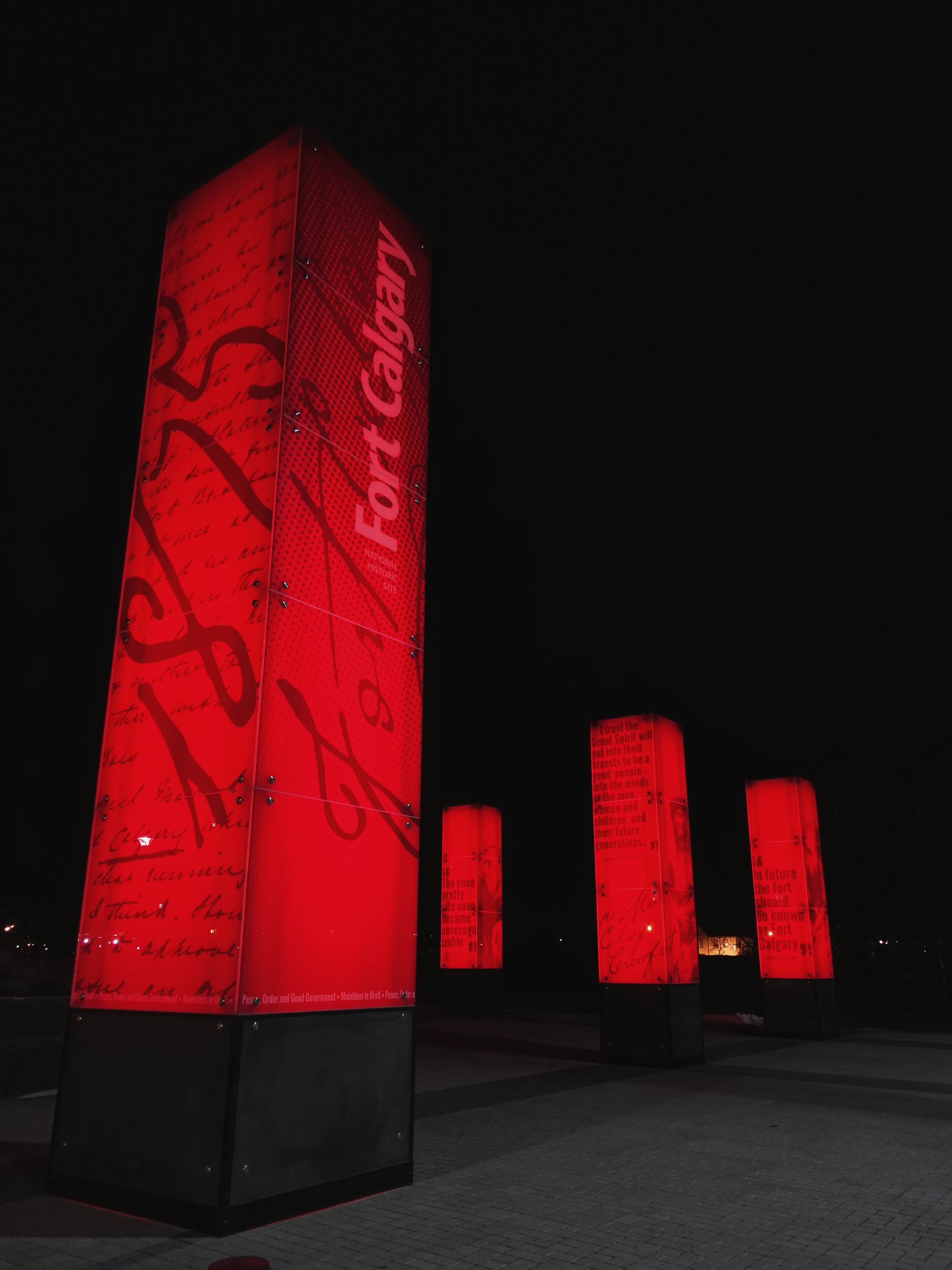 Fort Calgary's sentinels look like burning iron ingots at night, but the sidewalk and park are covered blackness.