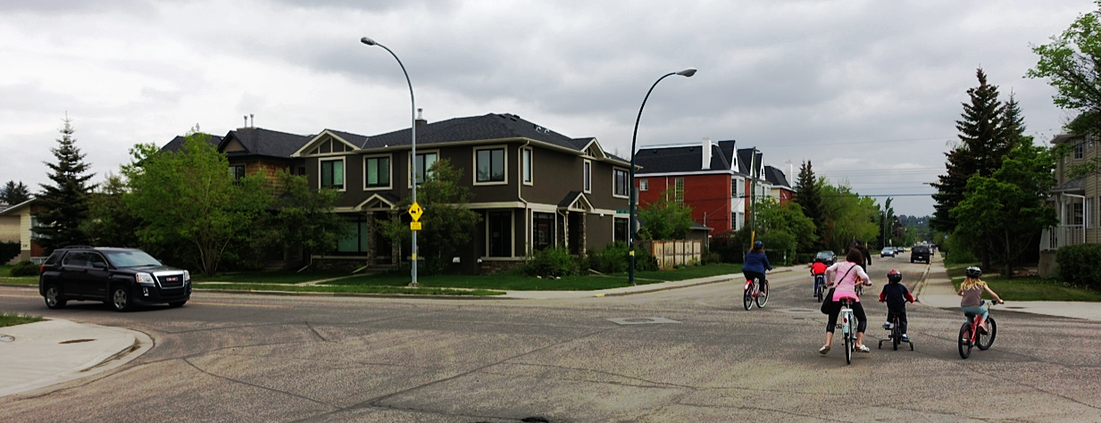 Cars routinely stop to let cyclists and pedestrians cross the road in Calgary.