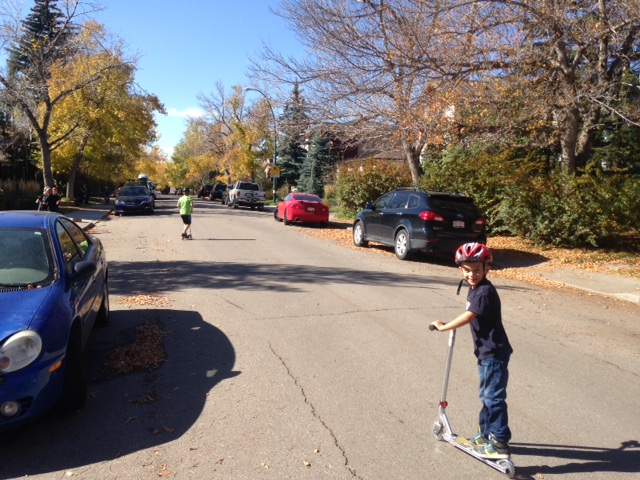 Boys weaving in and out of the cars on the open road. Note that where there are no parks cars it is far easier for drivers to see children playing on the sidewalk and for children to see the cars.