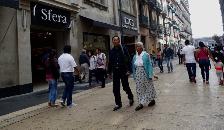 The streets of Mexico City are full of couples of all ages holding hands. Count the number of couples holding hands in this photo.