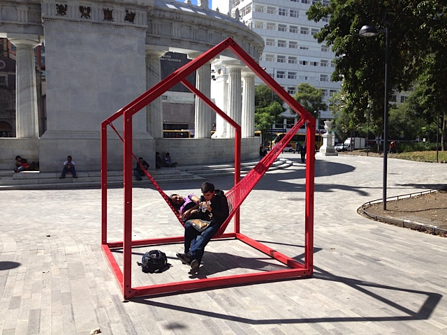 Young couple enjoying the temporary installation of red house shaped objects that supported a single hammock for Design Week.