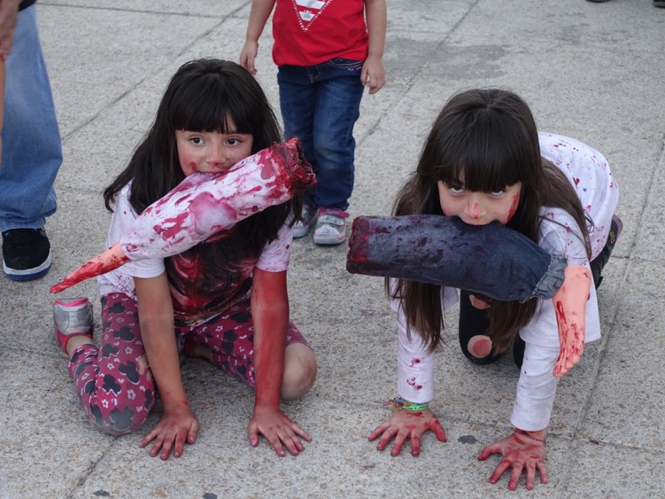 Two young girls crawling on the Revolution Plaza during the Zombie Walk.  Everyone was keen to have their picture taken that day and everyday in Mexico City.