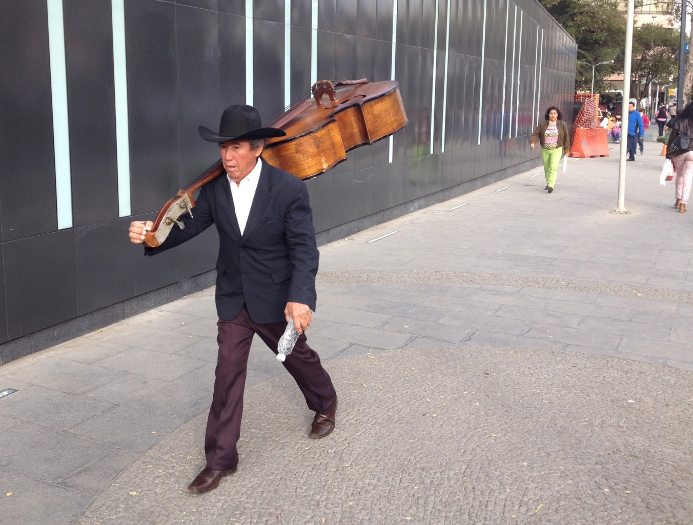 Musician walking to Revolution Subway station in Mexico City.