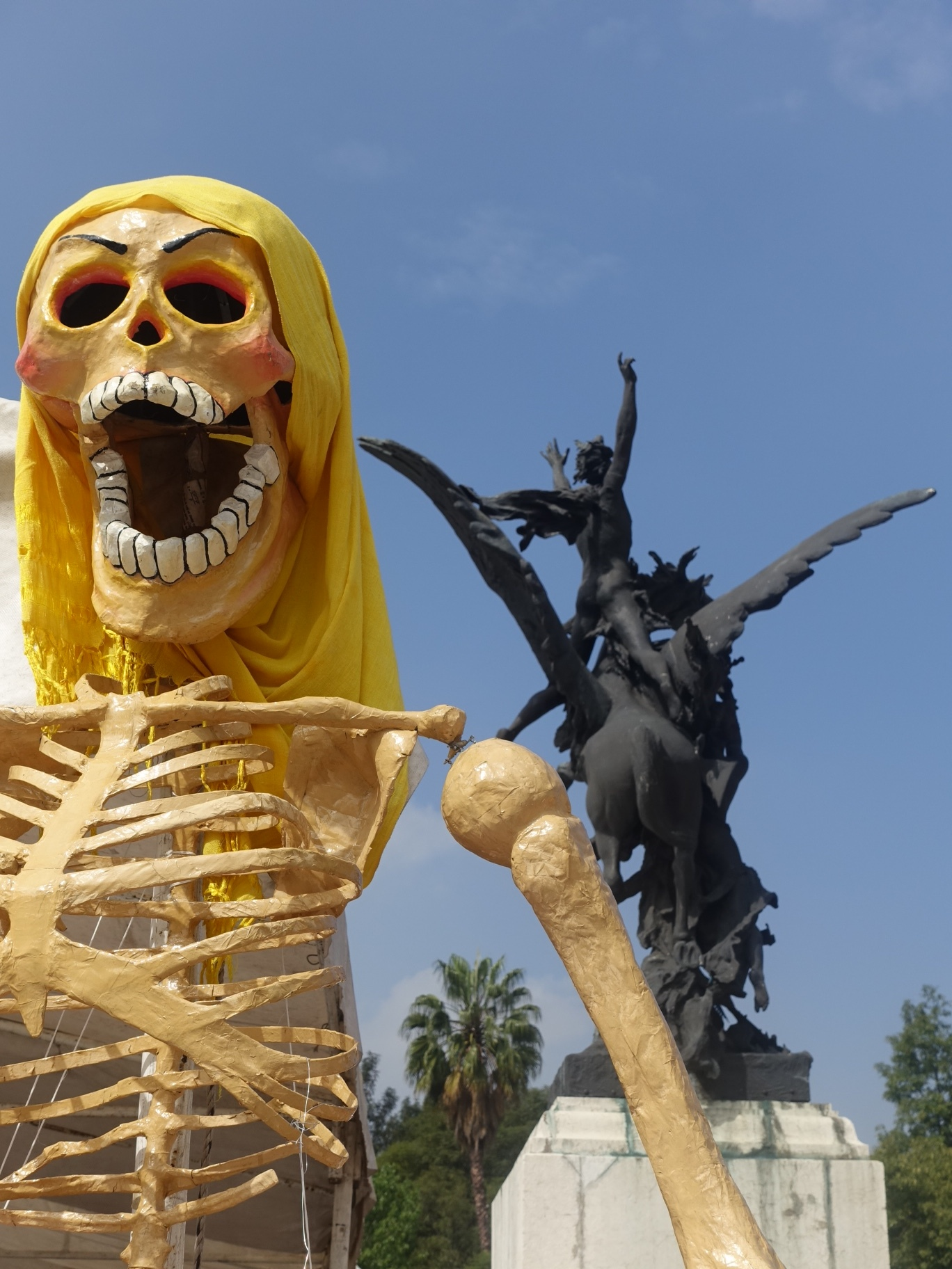 The juxtaposition of the colourful and temporary Day of the Dead skeleton figure with the permanent, dark winged-horse and figure statue captured my eye.  Located in the plaza in front of Mexico City's Bellas Artes concert hall.