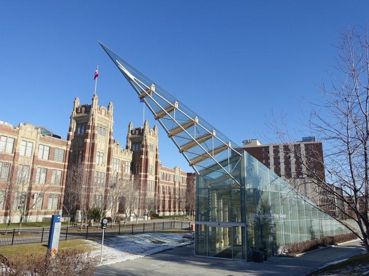 Glass pyramid entrance from campus ground level with Heritage Hall in the background.