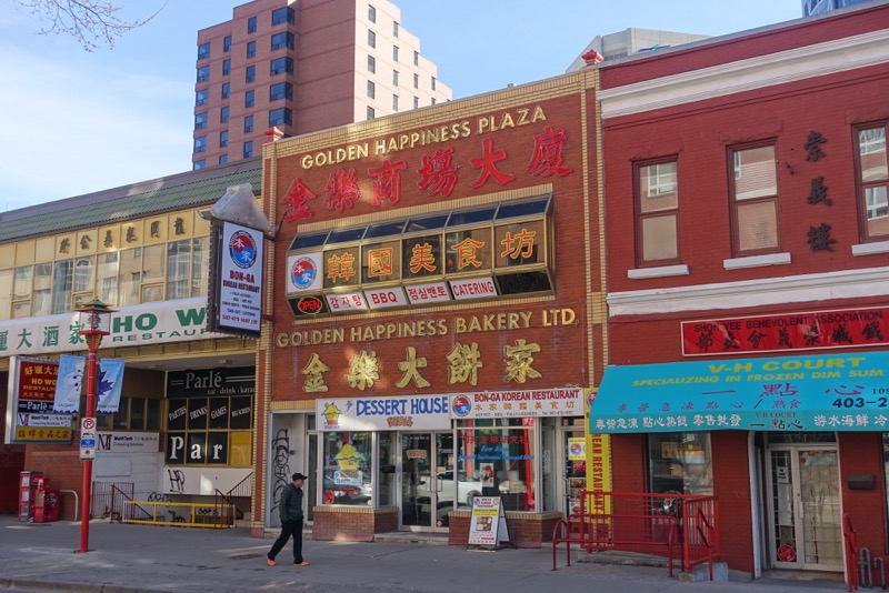 Flickering spring sun on Chinatown's Golden Happiness Plaza and Bakery.