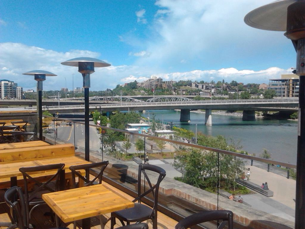 View of Bow River and East Village RiverWalk from roof-top patio of the Simmons building.