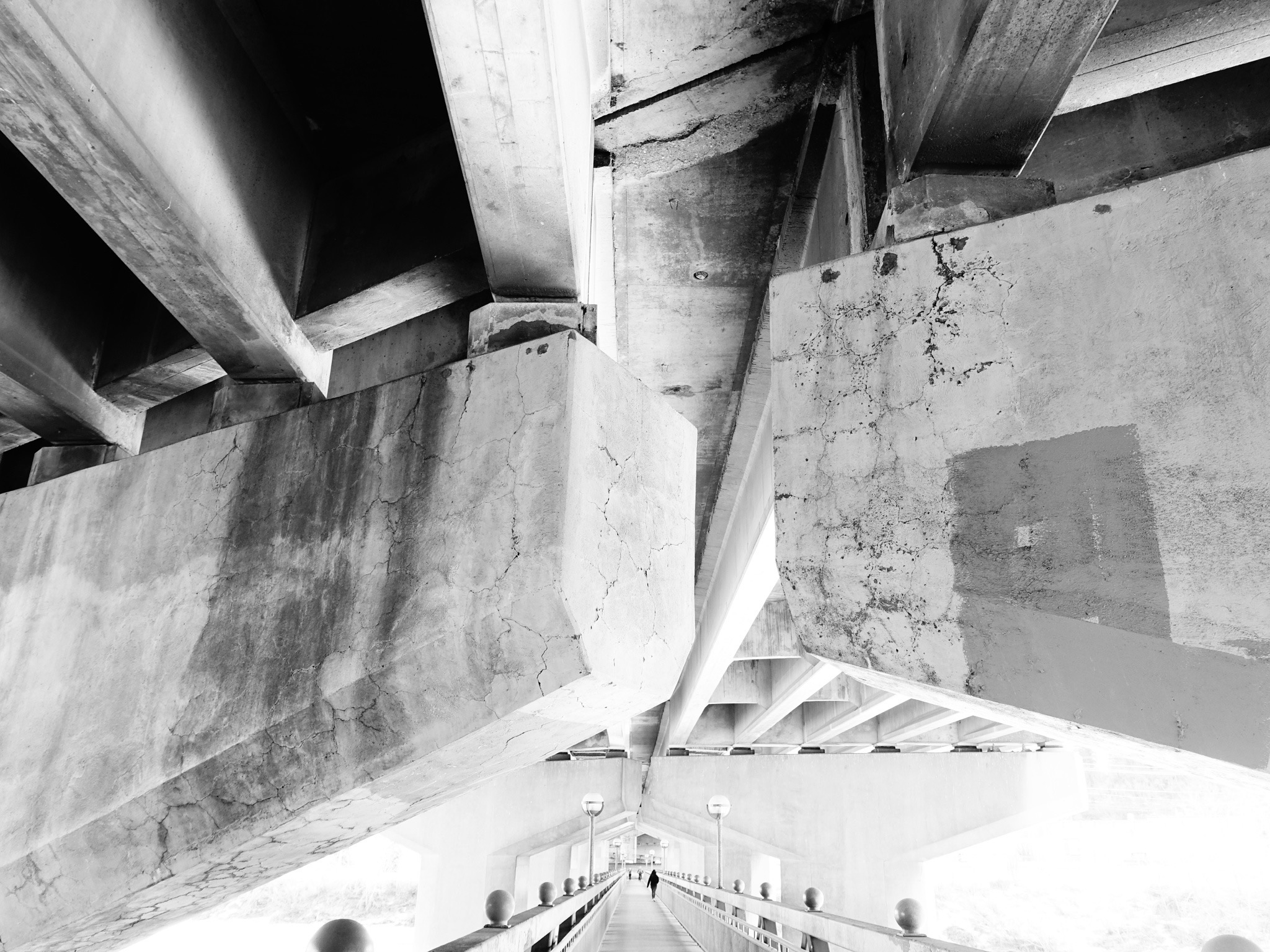I love this black and white photo of a lone walker on the Dave Freeze bridge that sits on the support columns of the Crowchild Trail bridge just above the Bow River.