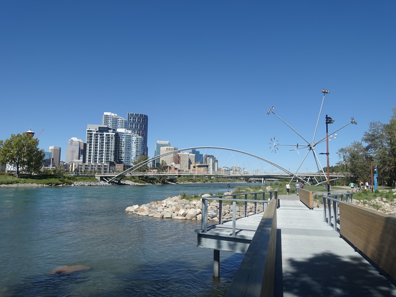East Village's pathways along the Bow River in St. Patrick's Island Park with the George King bridge in the background.