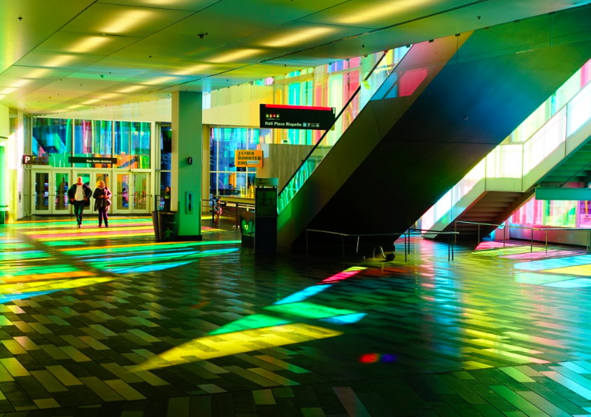 Captured this surreal light show at   south-west   entrance of the Montreal Convention Centre. The sun shining through the building's coloured glass facade created a wonderful mosaic on the escalator, steps, walls and floor inside the building. It is like walking into a stain glass window.