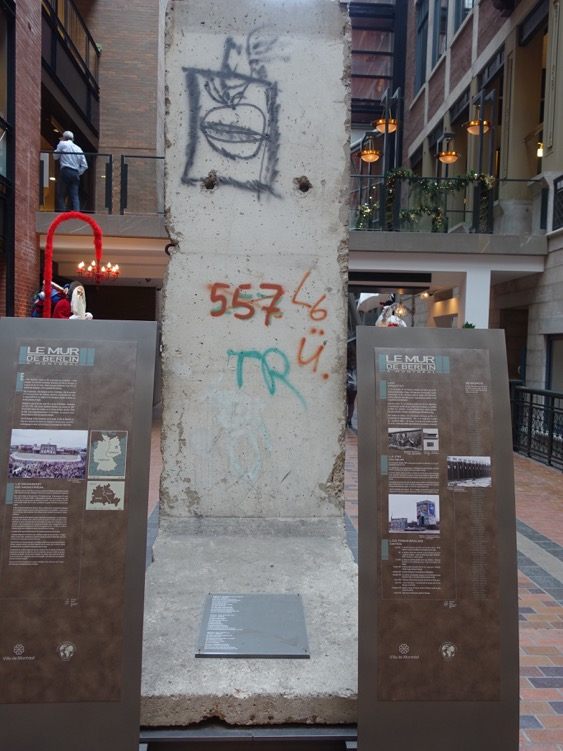 A remnant of the Berlin Wall, is on permanent display in the middle of the Ruelle des Fortifications in the lobby of the Montreal World Trade Center building. The lobby is located on the former site of Montreal's walled fortifications which were built in 1717 and demolished between 1804 and 1812.    The fragment, donated to the City of Montréal by the City of Berlin to commemorate Montréal's 350th anniversary, is a testament to Berlin's return to the community of free cities after the fall of the Wall on November 9, 1989.