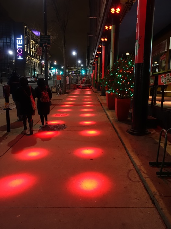 "This is not Montreal's ""Red Light District."" In several places we encountered red lights from buildings shining on the sidewalk creating a fun (and warm) pedestrian experience. I am interested in seeing how it works in the snow."