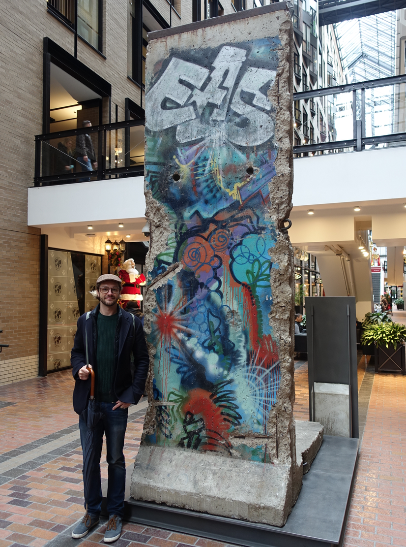 Tom beside a piece of the Berlin Wall located in a tunnel in Montreal's Quarter International.