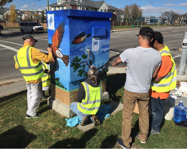 Driediger on the left working with the Crossroads community to add some ornamentation to their utility boxes.