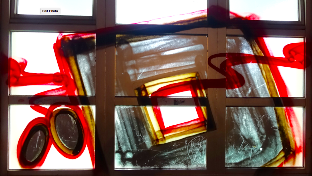 It is hard to take a photograph and not get some graffiti in it. This cropped stained-glass like   image   was on the window of a gym at night.