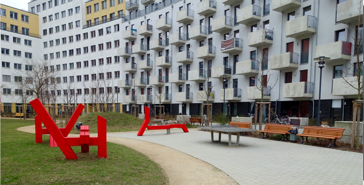 There is a small playground behind the hill in the background, along with these three red sculpture like pieces that could be used to sit on or to climb over or jump off of. Ping pong tables are also common in Berlin playground public spaces and yes they do get used.