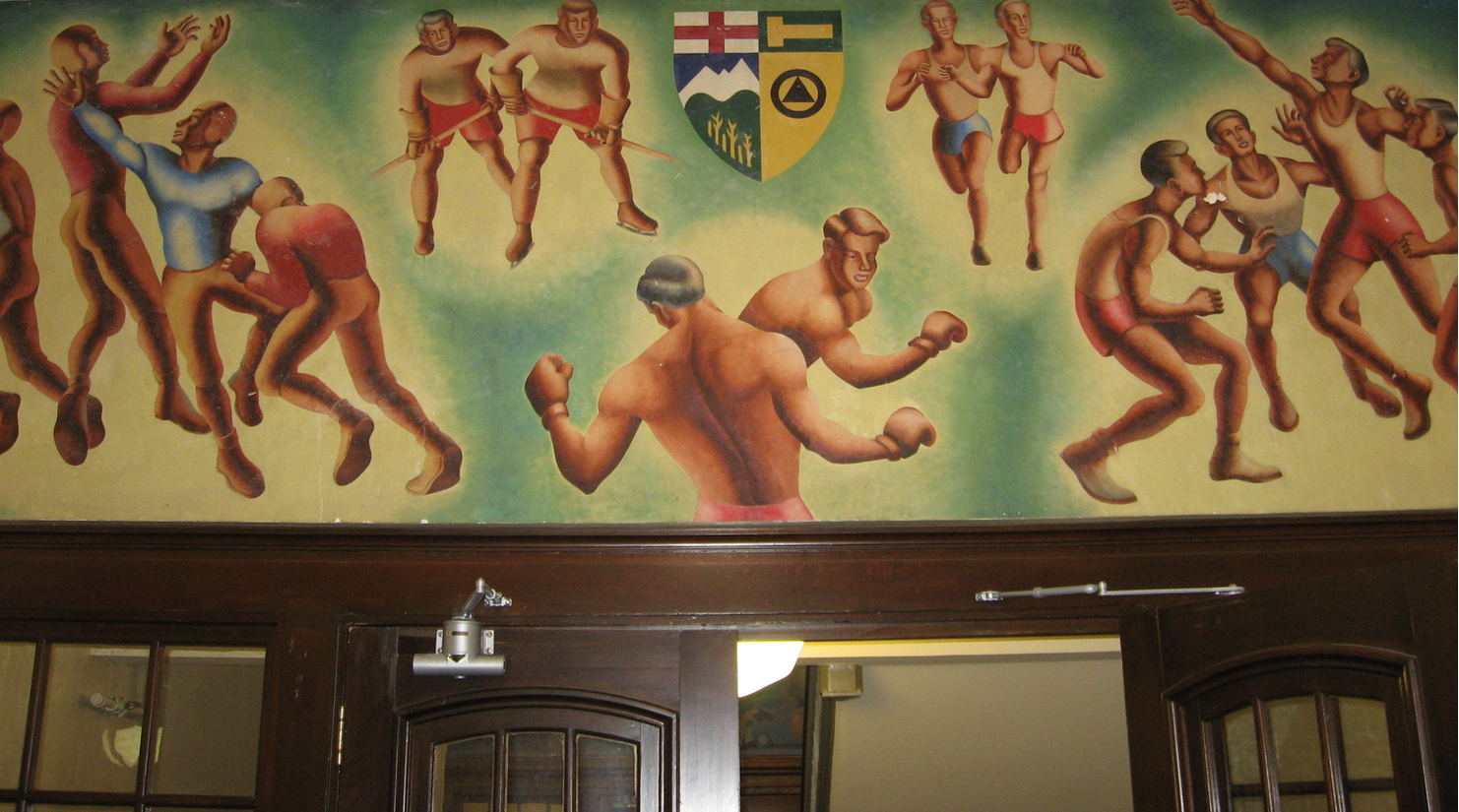 Murals above doorways in Heritage Hall.