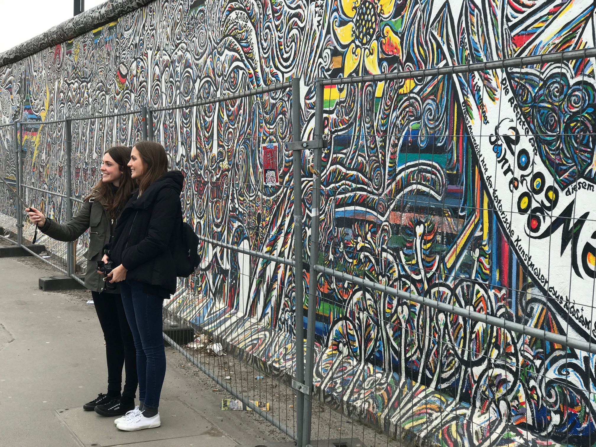 Tourists are more interested in selfies than looking at the art.  Perhaps you can't blame them when you have to look through a fence to see the art.