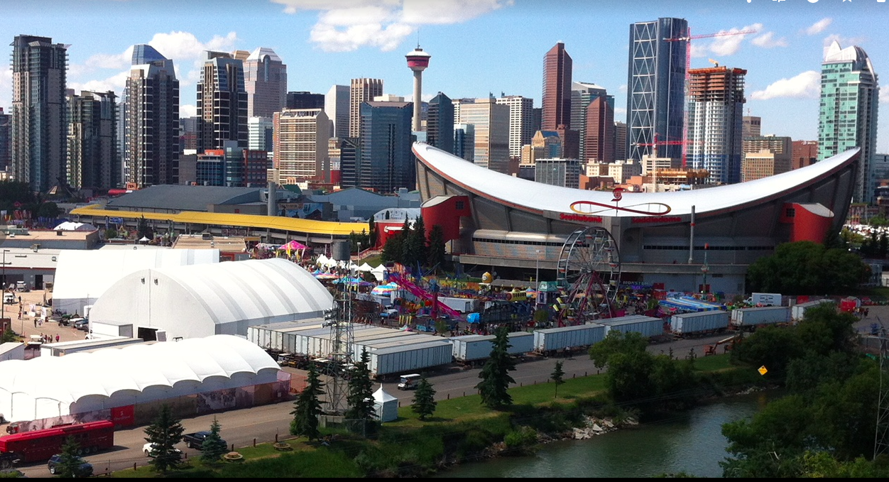 Calgary's Saddledome arena with downtown skyline in the background.