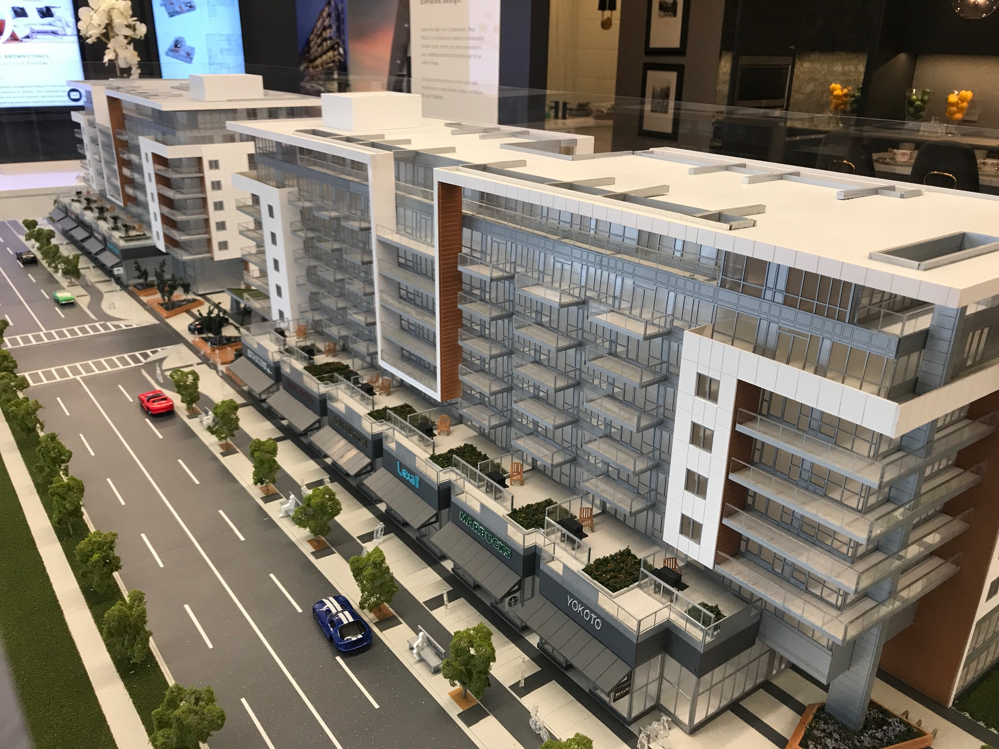 "Model of West District ""main street"" with retail at ground level and separate cycling lanes in the West District sales centre."