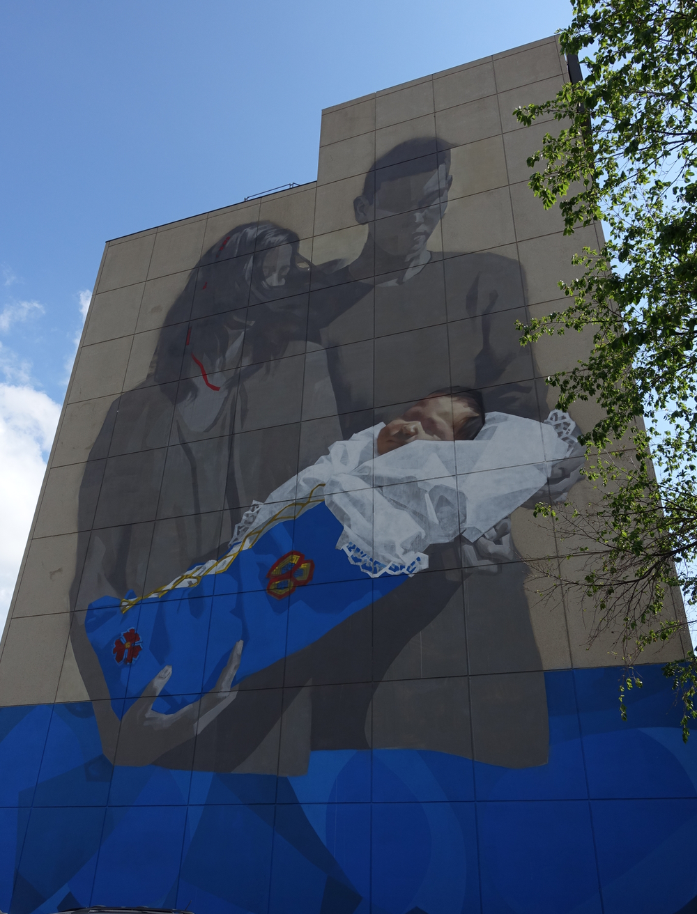 "I was gobsmacked by this nine storey tall mural on the side of the First Nations Bank building in downtown Saskatoon.      The mural was painted by Saskatchewan artist Emmanuel Jarus. I loved the tenderness that is depicted in such a large work.  While the child is obviously of indigenous descent, the parents are more ambiguous which allows for different interpretations.     Is it about new beginnings? Is it about the importance of family? Is is about love? Is it about dependence? Is it a contemporary interpretation of the ""mother and child"" image that has been part of painting history for centuries."