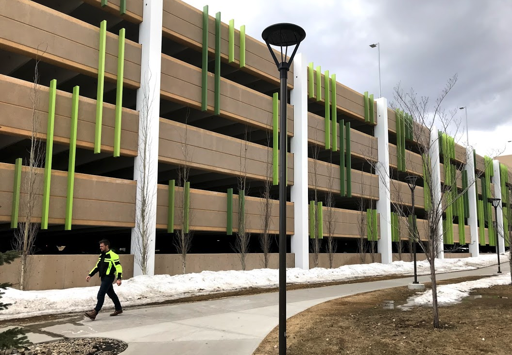 The new Mount Royal University's parade uses vertical neon green bars to break up what would have been a dull horizontal wall.