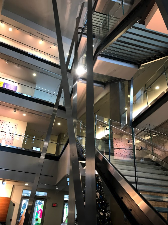 Escalator is a collaboration between Calgary artists Chris Cran and Gord Ferguson. It consists of nine stainless steel structural elements that not only serve as supports for the staircase, but also sense of play in the lobby of the building that is full of other artworks.