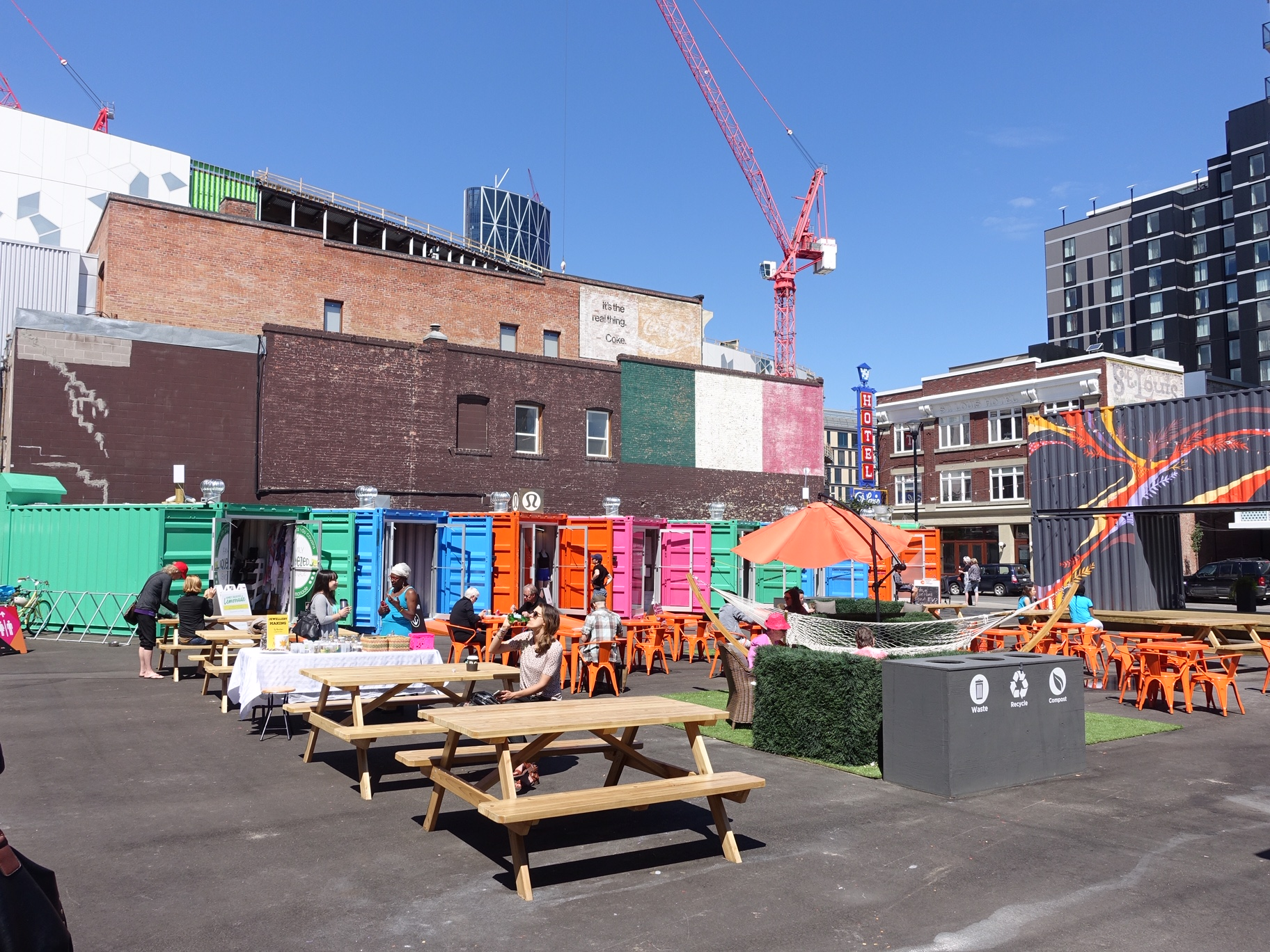 East Village's summer pop-up container park converts a surface parking lot into a funky people place thanks to CMLC. Eau Claire residents would love to see their parking lots programmed like this.