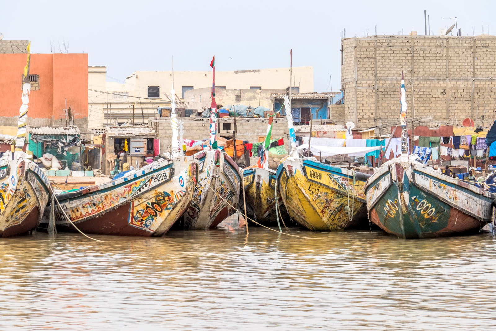 A group of colorful fishing boats in the harbor at St. Louis, Senegal. St. Louis is a major port for Senegal and a large portion of the people earn their living from the sea. Much of the fishing is done at night and the boats return in the morning to sell their catch.
