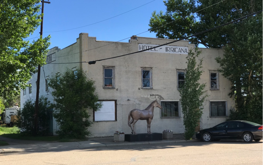 "The Irricana Hotel a reminder of the community's once bustling Main Street. Today ""Old Smoky"" stands guard. The plaque says the horse was fabricated by Kevan Leycraft and donated by Melvin Brown to commemorate his residence in Irricana since 1952. He passed away in 1997."
