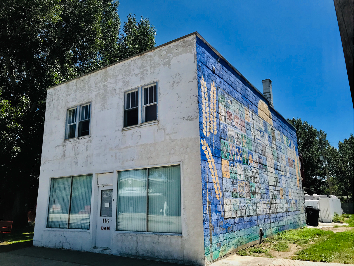 Someone has tried to brighten up this building and main street with a mural, but it has seen better days.