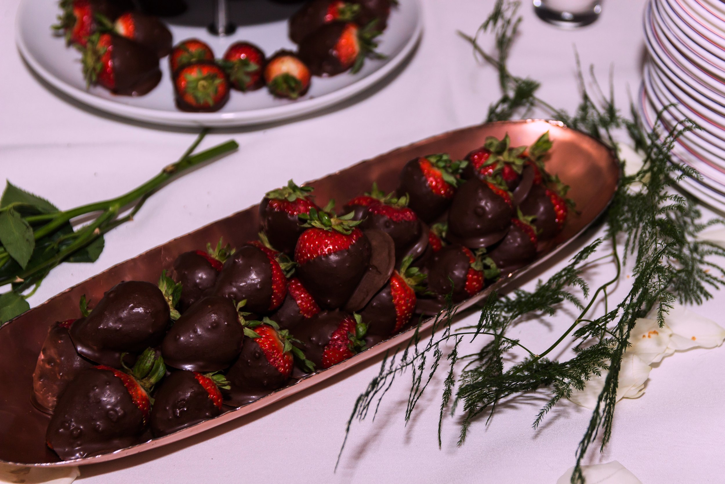Chocolate-dipped strawberries served in a gleaming copper plate