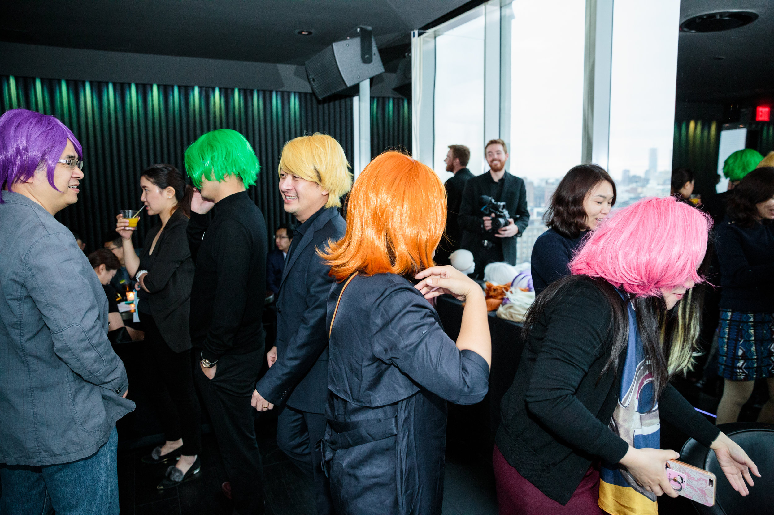 Guests sporting neon wigs as they mingle