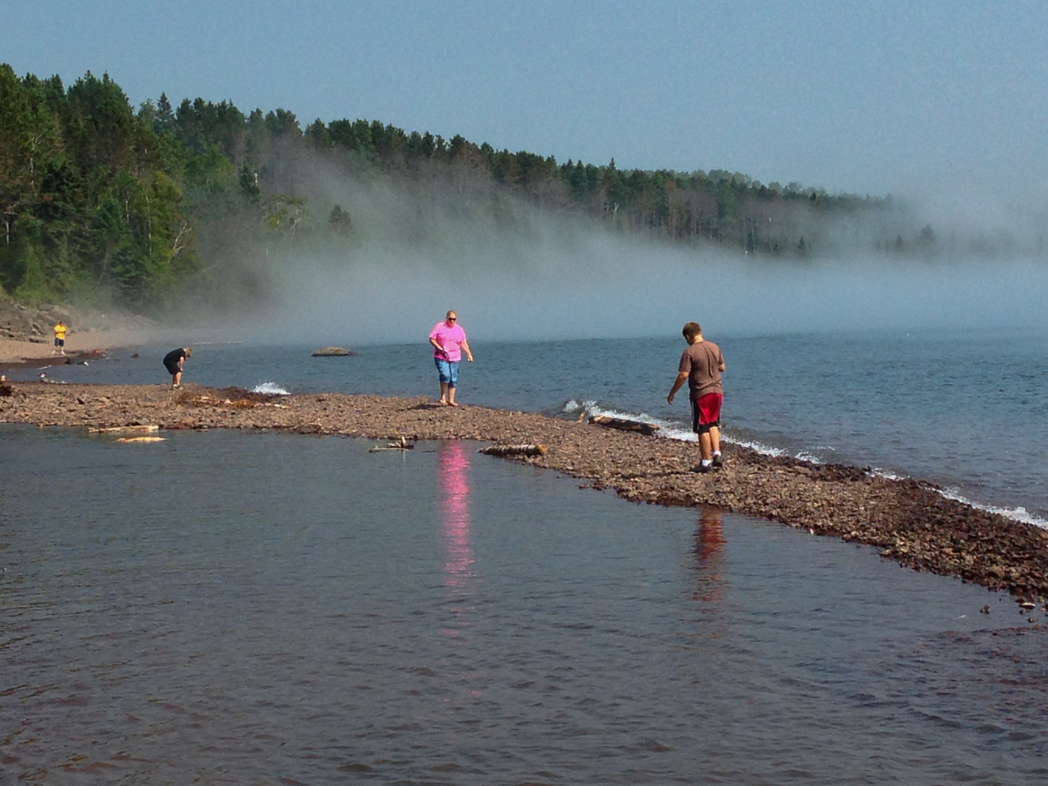 The family playing on the rocky beach of Lake Superior as the fog rolls in and out.