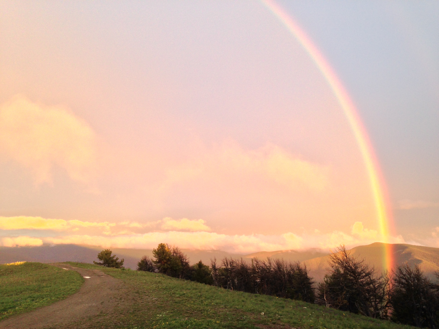 Rainbow between showers and sunset