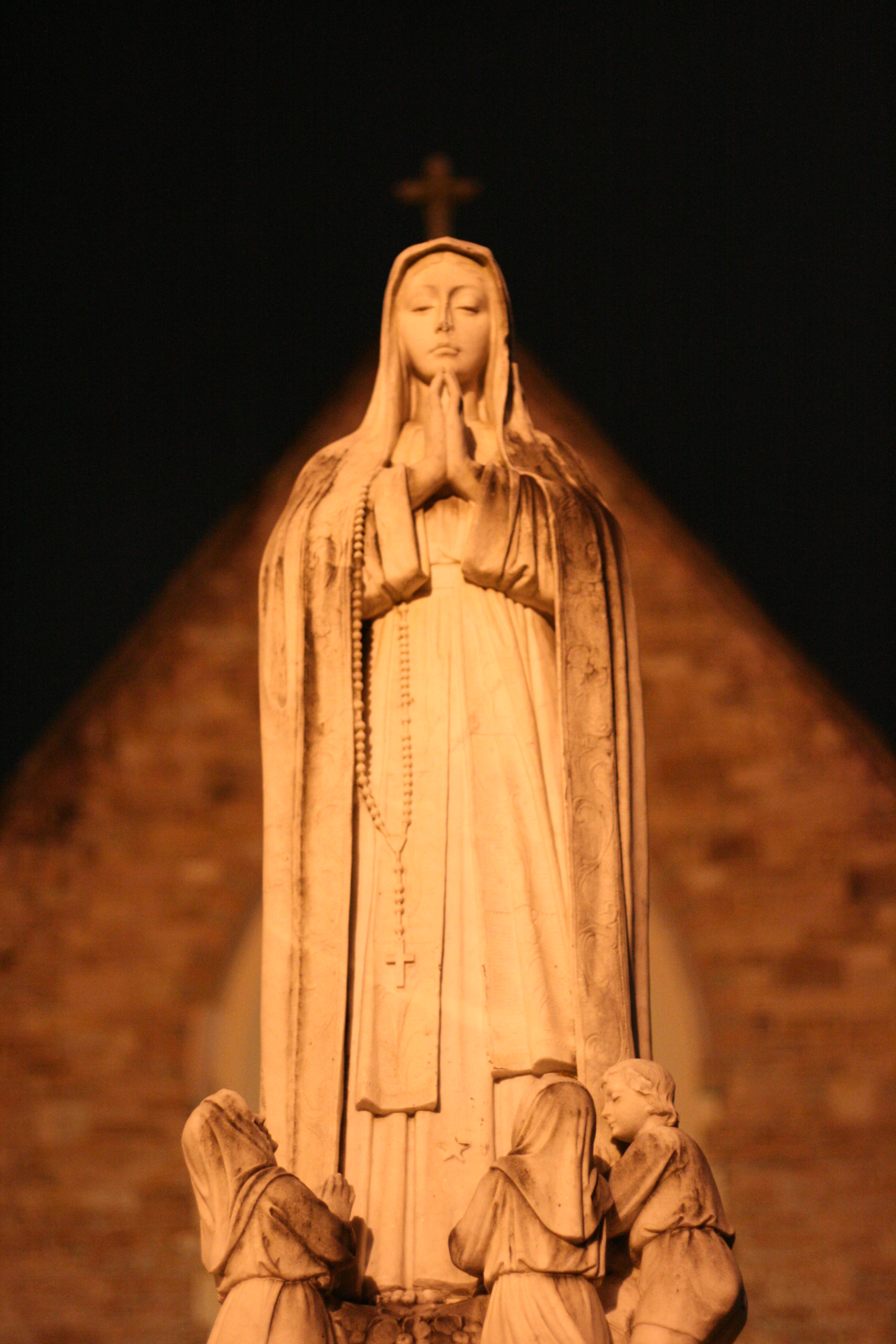 A statue of Mary Magdalene at a church at night