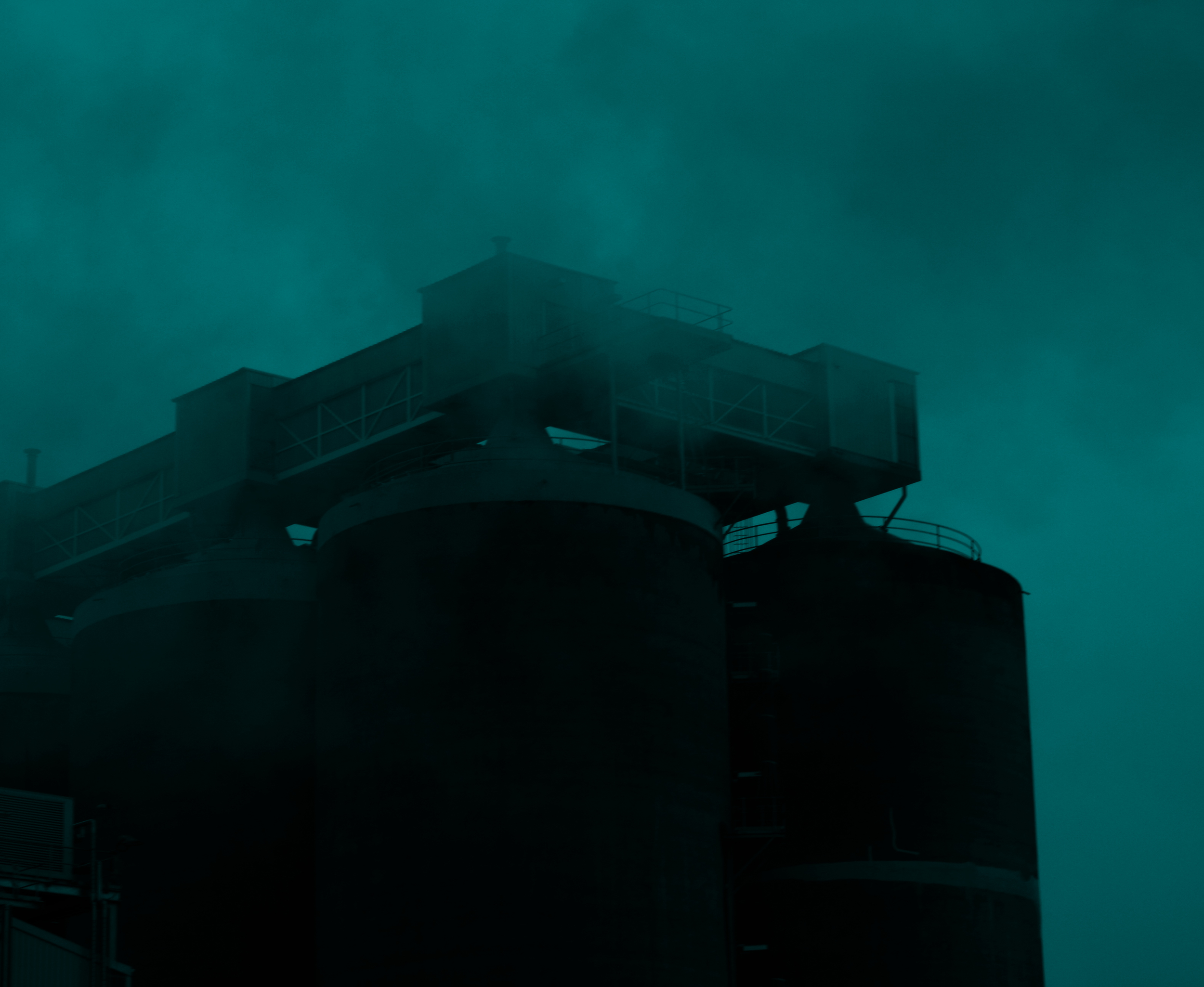Silos shrouded in ominous cloud in an industrial area.