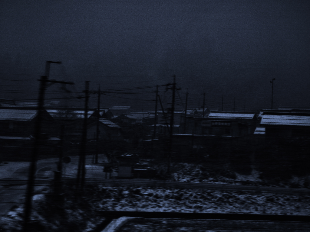 Dark, cold, snowy lands in an industrial area bordered by residential houses in the outskirts of Kyoto, Japan.