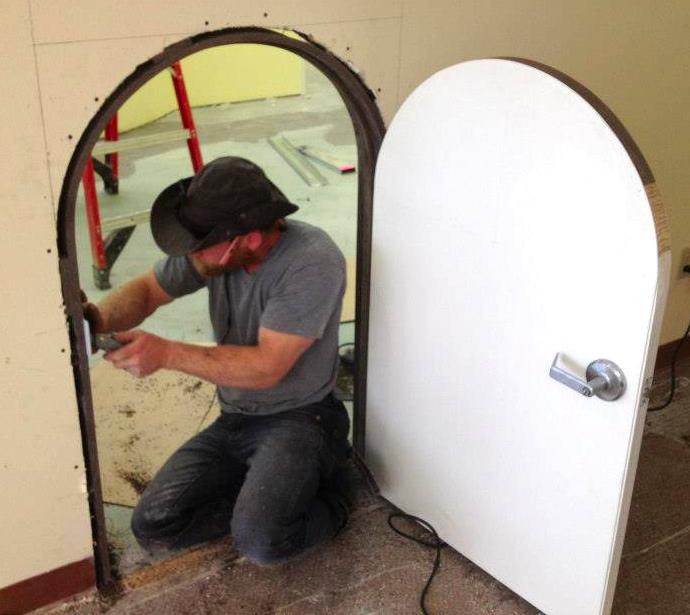 Carpenter installing custom build children's' door.