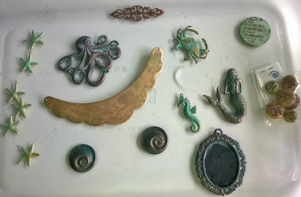 Brass necklace blank, starfish, shells, octopus, crab, seahorse, mermaid and other interesting bits that all needed to be together. The blank, seashells, starfish and bezel had a fresh coat of Swellegant brushed on the surface.